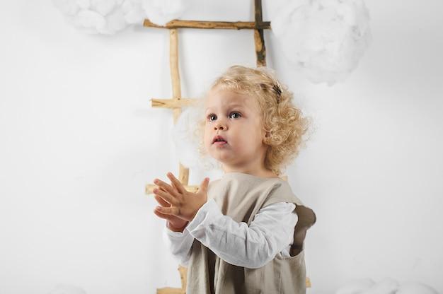 Porträt eines kleinen mädchens nahe der leiter inmitten der wolken auf einem weißen hintergrund