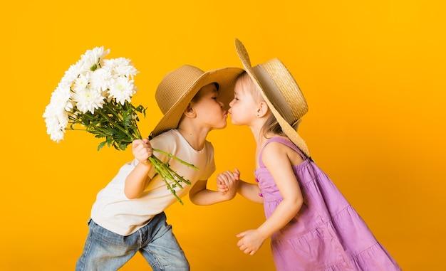 Porträt eines kleinen mädchens und eines jungen in strohhüten, die auf einer gelben oberfläche mit platz für text küssen. ein junge hält einen strauß weißer blumen