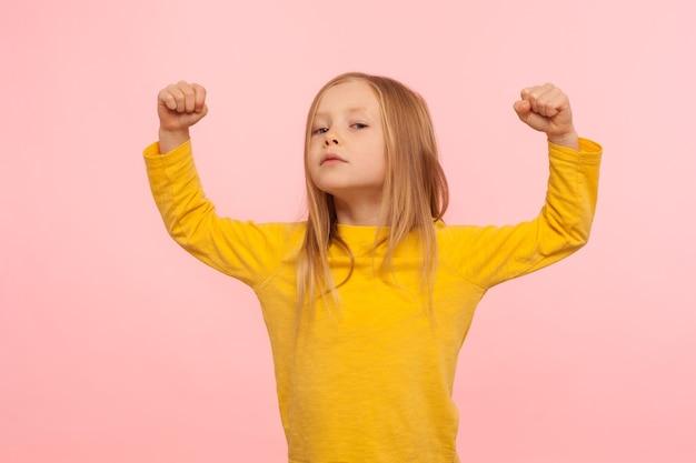 Porträt eines kleinen mutigen mädchens, das mit erhobenen fäusten steht, macht in kleinen händen zeigt und mit arroganz, konzept der stärke, selbstvertrauen schaut. studioaufnahme isoliert auf rosa hintergrund