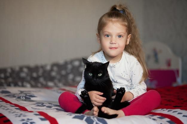 Porträt eines kleinen niedlichen kindermädchens, das eine schwarze katze mit zärtlichkeit und liebe umarmt und vor glück lächelt