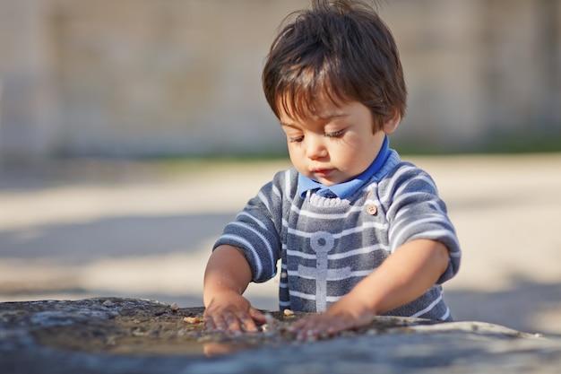 Porträt eines kleinen östlichen hübschen jungen, der draußen im park spielt