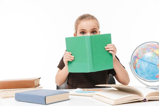 Porträt eines kleinen schulmädchens, das bücher liest und hausaufgaben macht, während es am schreibtisch in der klasse sitzt, isoliert über weißer wand