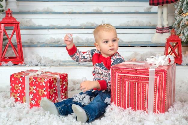Porträt eines kleinen süßen jungen mit einem geschenk in den händen in der nähe des weihnachtsbaums zu weihnachten