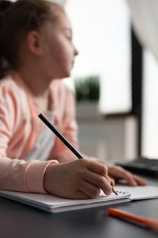 Porträt eines klugen schulmädchens, das online-klasse hört