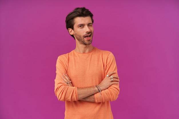 Porträt eines koketten mannes mit brünetten haaren und borsten. tragen eines orangefarbenen pullovers mit hochgekrempelten ärmeln. hat armbänder und ringe. hält die arme verschränkt