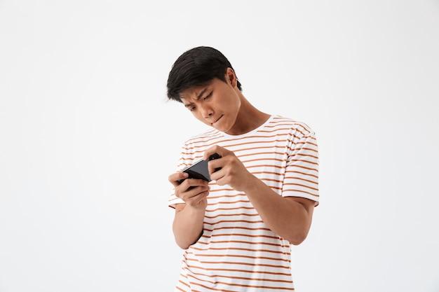 Porträt eines konzentrierten jungen asiatischen mannes, der spielt