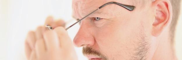 Porträt eines konzentrierten männlichen mannes, der seine brille abnimmt