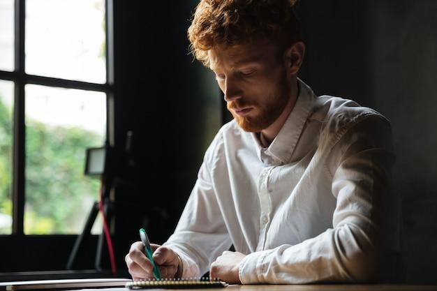 Porträt eines konzentrierten rothaarigen mannes, der in ein notizbuch schreibt