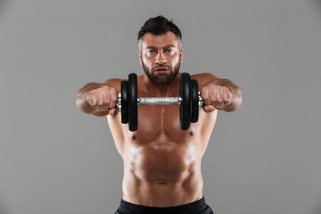Porträt eines konzentrierten starken hemdlosen männlichen bodybuilders