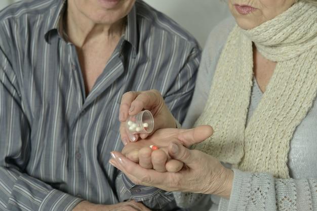 Porträt eines kranken älteren ehepaares mit pillen