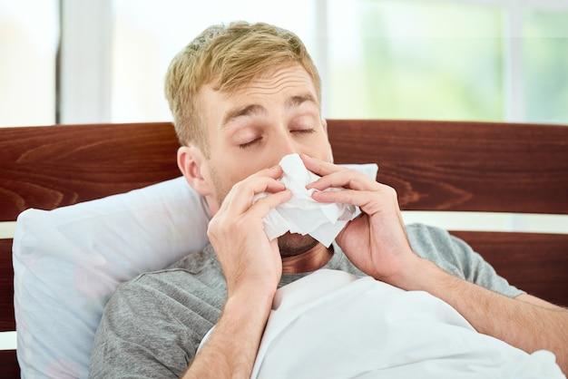 Porträt eines kranken jungen mannes mit laufender nase, der an erkältung oder grippe leidet und