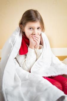 Porträt eines kranken kleinen mädchens, das auf dem bett unter der decke hustet