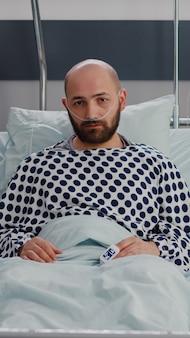 Porträt eines kranken mannes, der im bett ruht und auf eine atemwegsbehandlung wartet