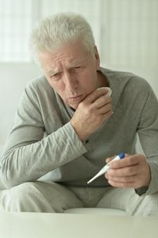 Porträt eines kranken reifen mannes mit thermometer