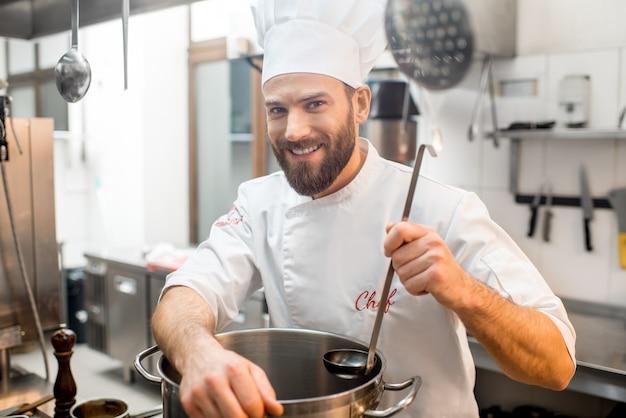 Porträt eines küchenchefs in uniform mit großem herd in der restaurantküche