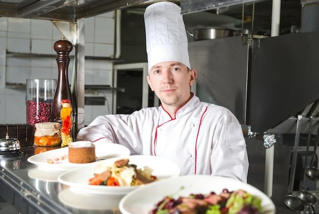 Porträt eines küchenchefs mit gekochtem essen in der küche im restaurant.