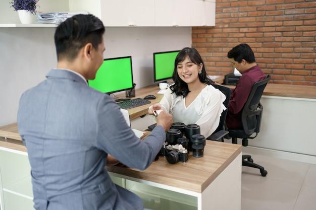 Porträt eines kunden bezahlen die rechnung mit kreditkarte im kameraverleih