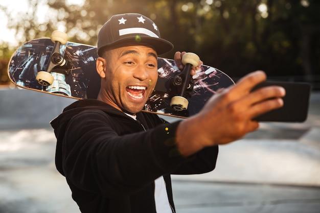 Porträt eines lachenden afrikanischen männlichen teenagers, der ein selfie nimmt