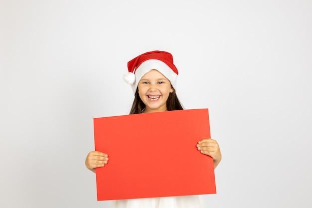 Porträt eines lachenden kaukasischen mädchens in weißem kleid und weihnachtsmann-hut mit rotem leerem poster-isolier...