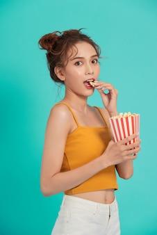 Porträt eines lachenden mädchens in der freizeitkleidung, die popcornbox hält