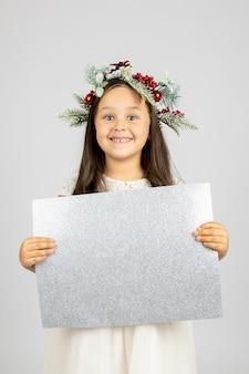 Porträt eines lachenden mädchens in weißem kleid und weihnachtskranz mit silbernem, glänzendem leerem poster isol...