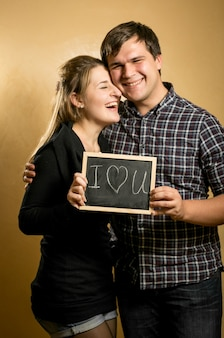 Porträt eines lachenden verliebten paares, das tafel mit geschriebenem wort
