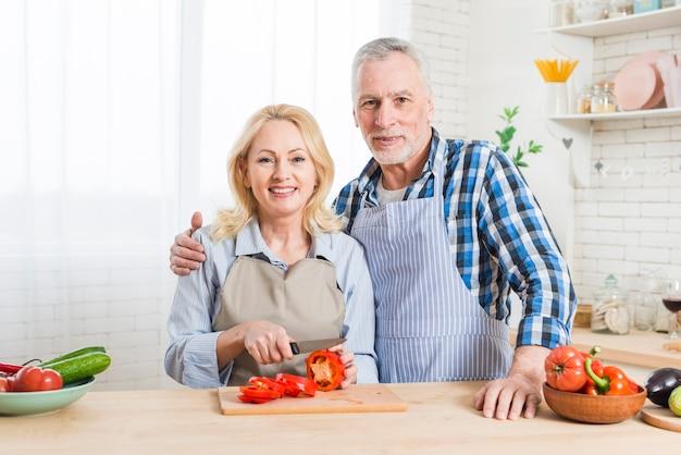 Porträt eines lächelnden älteren paares, das in der küche steht