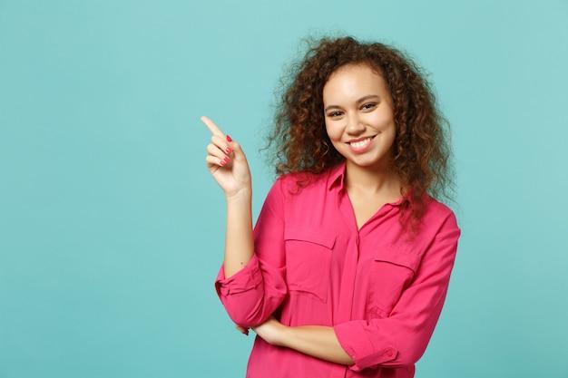 Porträt eines lächelnden afrikanischen mädchens in rosafarbener freizeitkleidung, das den zeigefinger beiseite zeigt, isoliert auf blauem türkisfarbenem wandhintergrund im studio. menschen aufrichtige emotionen lifestyle-konzept. kopieren sie platz.