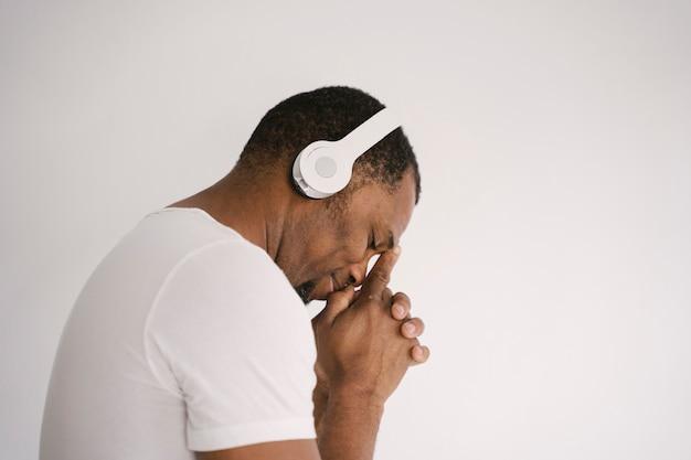 Porträt eines lächelnden afroamerikanermannes, der musik auf kopfhörern denkend hört.