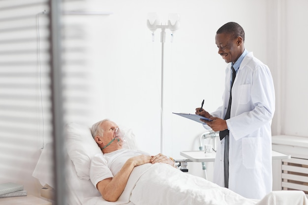 Porträt eines lächelnden afroamerikanischen arztes, der sich um einen älteren mann kümmert, der im krankenhausbett mit sauerstoffergänzungsmaske liegt, kopierraum