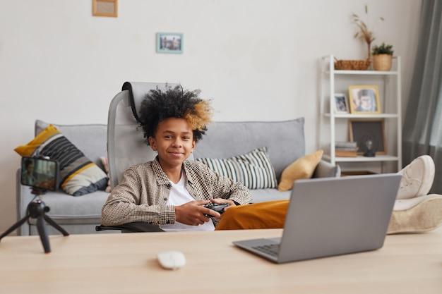 Porträt eines lächelnden afroamerikanischen jungen, der zu hause videospiele spielt und online-streaming, junges gamer- oder blogger-konzept, kopierraum