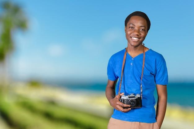Porträt eines lächelnden afroamerikanischen mannes, der foto auf retro- kamera macht