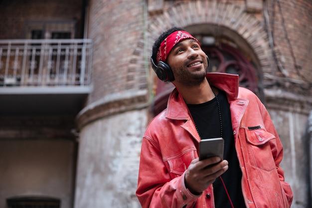 Porträt eines lächelnden afroamerikanischen mannes, der musik hört