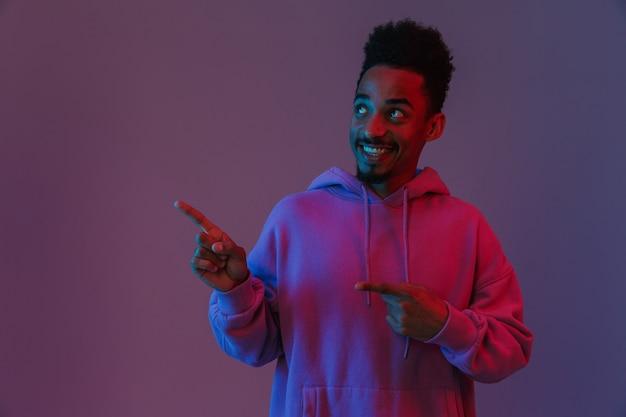 Porträt eines lächelnden afroamerikanischen mannes in buntem hoodie, der mit den fingern isoliert über der violetten wand beiseite schaut und zeigt