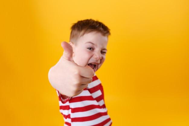 Porträt eines lächelnden aktiven kleinen jungen, der daumen hoch zeigt