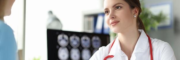 Porträt eines lächelnden arztes, der an einem patiententermin teilnimmt