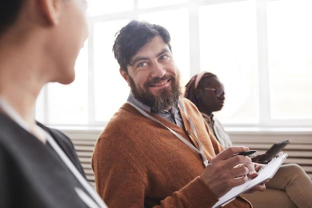 Porträt eines lächelnden bärtigen mannes im publikum bei konferenzen oder geschäftsseminaren, kopienraum