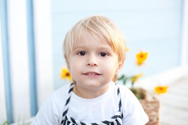 Porträt eines lächelnden blonden kleinen jungen im freien. charmantes kind, das sommerzeit im park verbringt, im freien aufwirft, direkt in die kamera schaut, gekleidet in ein weißes lässiges t-shirt. kindheitskonzept.