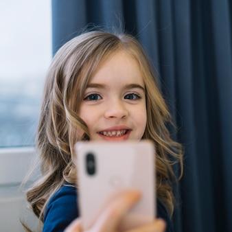 Porträt eines lächelnden blonden mädchens, das selbstporträt am handy nimmt