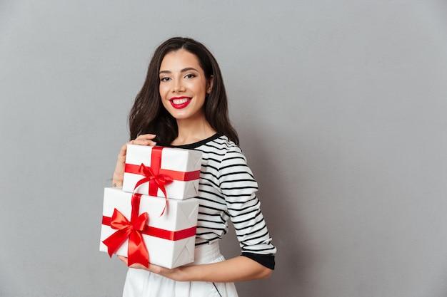 Porträt eines lächelnden frauenholdingstapels geschenkboxen