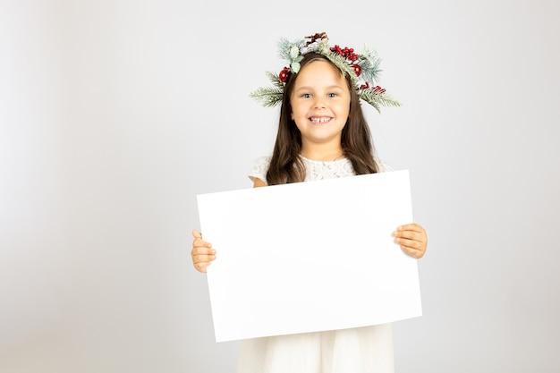 Porträt eines lächelnden fröhlichen mädchens im weihnachtskranz aus tannenzweigen mit weißem leerem papier isoliert ...