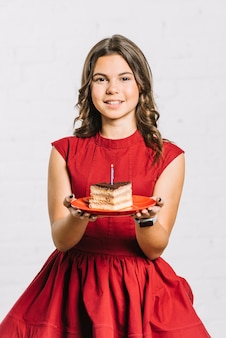 Porträt eines lächelnden geburtstagsmädchens, das eine scheibe des kuchens auf platte mit einer belichteten kerze hält