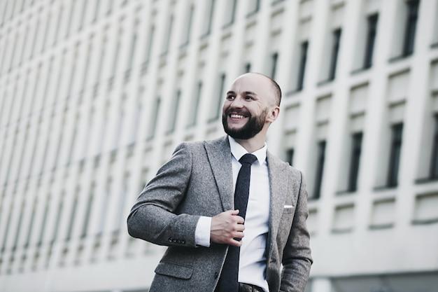 Porträt eines lächelnden geschäftsmannes. glücklicher mann, der im stadtbild aufwirft.