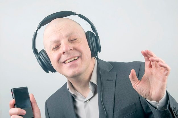 Porträt eines lächelnden geschäftsmannes mit kopfhörern und einem mp3-player