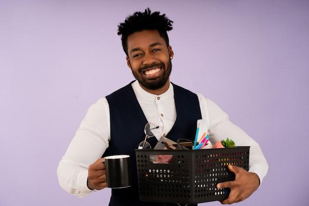 Porträt eines lächelnden geschäftsmannes, während er eine kiste mit persönlichen gegenständen für das büro hält. geschäftskonzept.