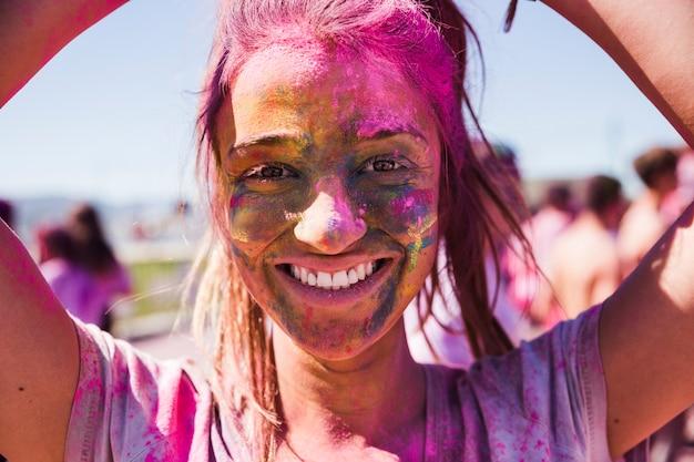 Porträt eines lächelnden gesichtes der jungen frau bedeckt mit holi farbe