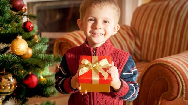Porträt eines lächelnden, glücklichen kleinen jungen, der seine weihnachtsgeschenkbox vom weihnachtsmann hält und neben dem weihnachtsbaum im wohnzimmer steht