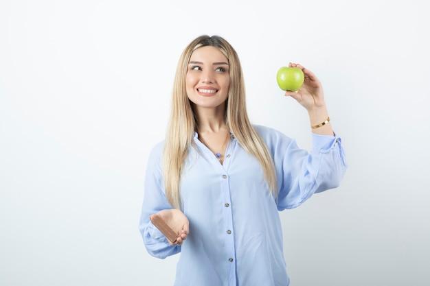 Porträt eines lächelnden glücklichen mädchens, das grünen apfel mit schokoriegel gegen weiße wand hält