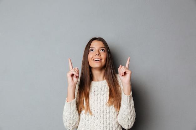 Porträt eines lächelnden glücklichen mädchens, das zwei finger nach oben zeigt