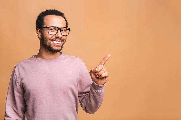 Porträt eines lächelnden glücklichen mannes im lässigen zeigen mit den fingern beiseite lokalisiert über beige.